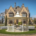 """""""Lady Leticia Dream Carousel"""" Bandstand Pavilion in Use Outside Manor House - Manor By The Lake"""