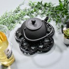 Black Cast Iron Flower Trivet in Use with Teapot