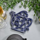 Blue Cast Iron Kettle Trivet on Blue Table