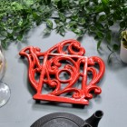 Red Cast Iron Kettle Trivet in Situ on Blue Table