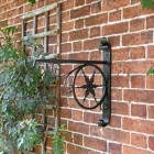 """Northern Star"" Hanging Basket Bracket in Situ on a Brick Wall"