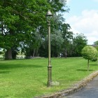 Olive Green Opulent Cast Iron Lamp Post In Garden Setting