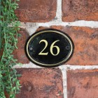 Polished Brass & Black Oval House Number Sign With Vinyl Numbers on a Brick Wall