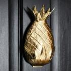 Polished brass pineapple door knocker on a black door