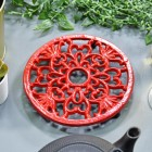 Red Heavy Duty Cast Iron Round Trivet in Situ on a Table