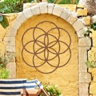 "Rustic ""Seed of Life"" Steel Wall Art on a Yellow Garden Wall"