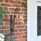 Black Scrolled Hanging Basket Bracket in Situ Net to the Front Door