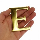 """Polished Brass Letter """"E"""" in hand"""