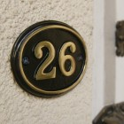 Close up of polished brass & black oval house number