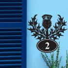 Thistle Iron House Number Sign in Situ on a Blue Wall