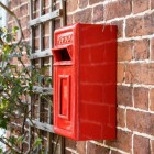 Traditional Red & Gold Wall Mounted Post Box Mounted on a Brick Wall