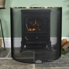 Modern Black Rounded Fire Screen With Polished Brass Trim In Front Of Stove