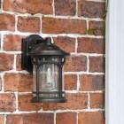 Bronze wall light in situ next to door frame