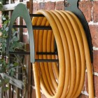 Side View of the Wall Mounted Sitting Fox Iron Hose Holder Mounted to a Brick Wall