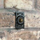 Black Traditional Rectangular Door Bell Push in Situ on a Brick Wall
