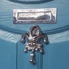 Bright Chrome Jester door knocker on Blue door