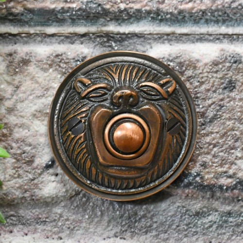 Burnished Copper Lion face bell push on brick wall