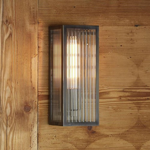 Rubbed Bronze Reeded Glass Wall Light in Situ on a Wooden Wall