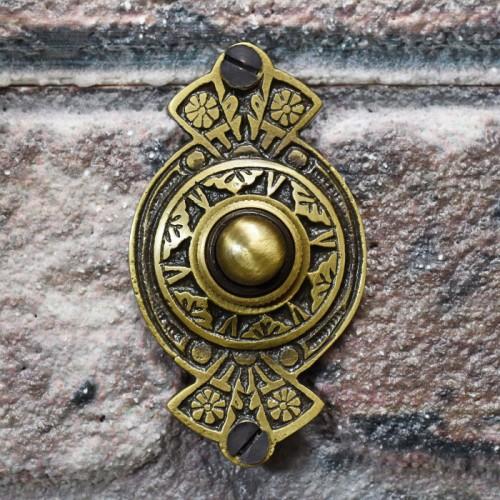 Antique Brass door bell on brick wall