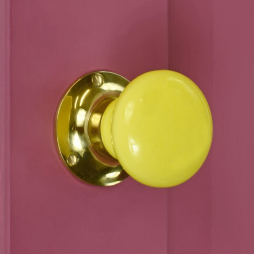 Bright yellow door knob on pink door with brass backplate