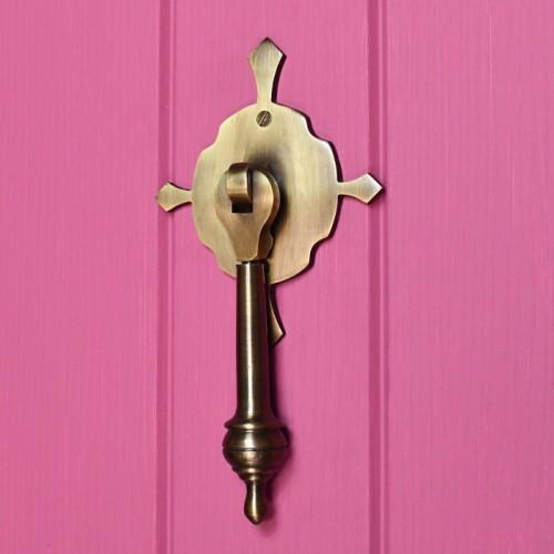 Antique Brass pendulum door knocker on pink door
