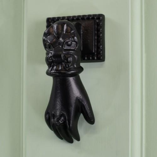 Black Hand door knocker on pale green door