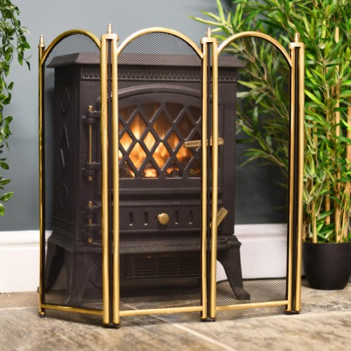 4 fold polished brass fireguard infornt of log burner