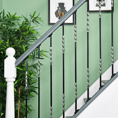 """Rabanne"" Stainless Steel Stair Spindle in Use by a Green Wall"