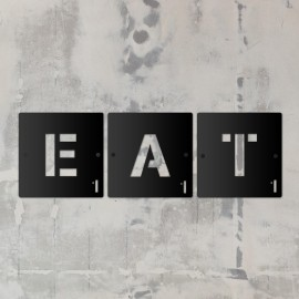 'EAT' Black Scrabble Square Letters in situ on a Rustic Wall
