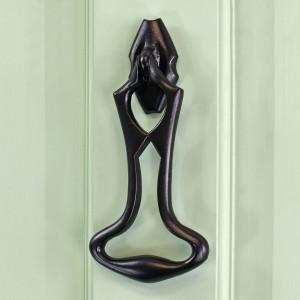 Black Iron Art Deco Door Knocker on green wood Door