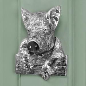 Bright Chrome Pig door knocker on green door
