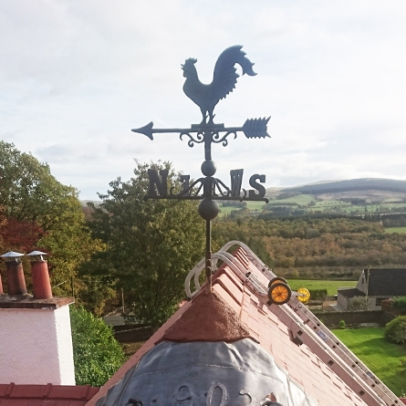 Rooster weathervane mounted on a roof