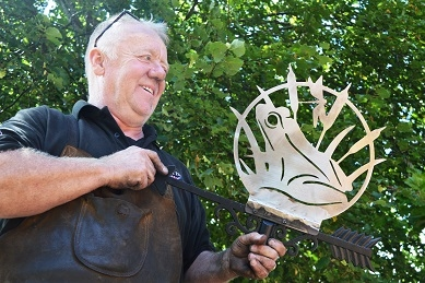 Blacksmith creating a frog design weathervane