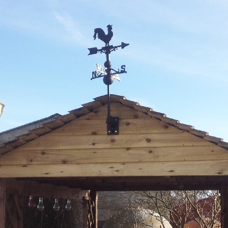 Mini rooster weathervane mounted on a garden pergola